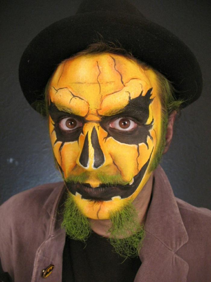 maquillage homme citrouille, moustache verte, lèvres noires, grandes ombres en noir foncé autour des yeux, chapeau