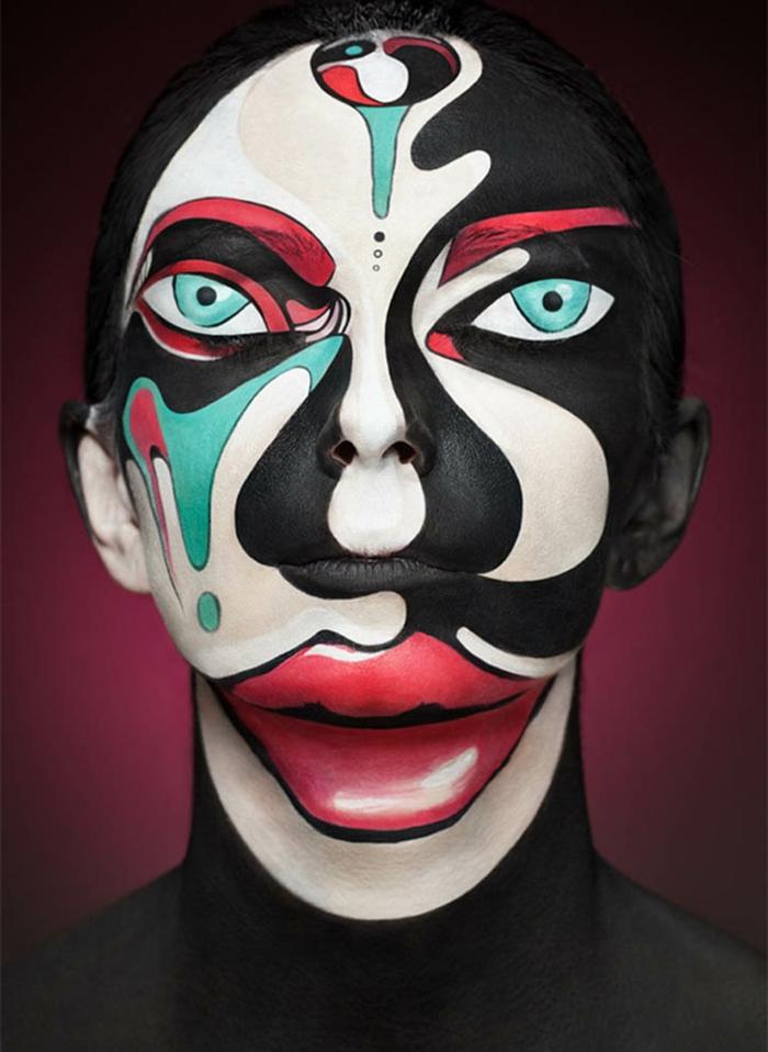 maquillage de halloween extraordinaire avec peintures bleue noire et blanche, yeux dessinés sur les paupières, grande bouche grottesque