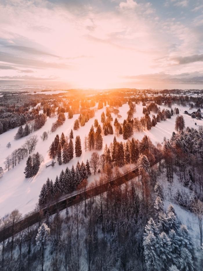 incroyable paysage hiver au coucher du soleil dans les montagnes, photo forêt aux arbres enneigés et ciel nuageux