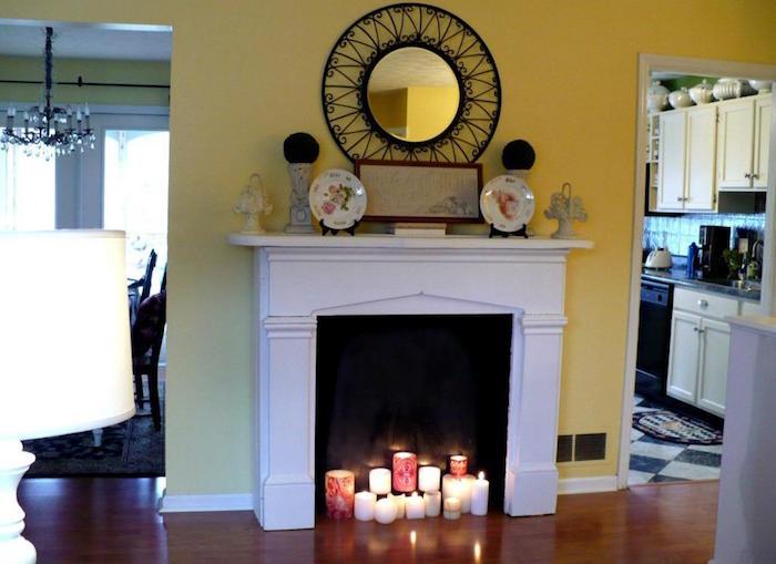 cheminée décorative avec manteau simple blanc dans salon mur jaune et lot de bougies dans insert à fond noir