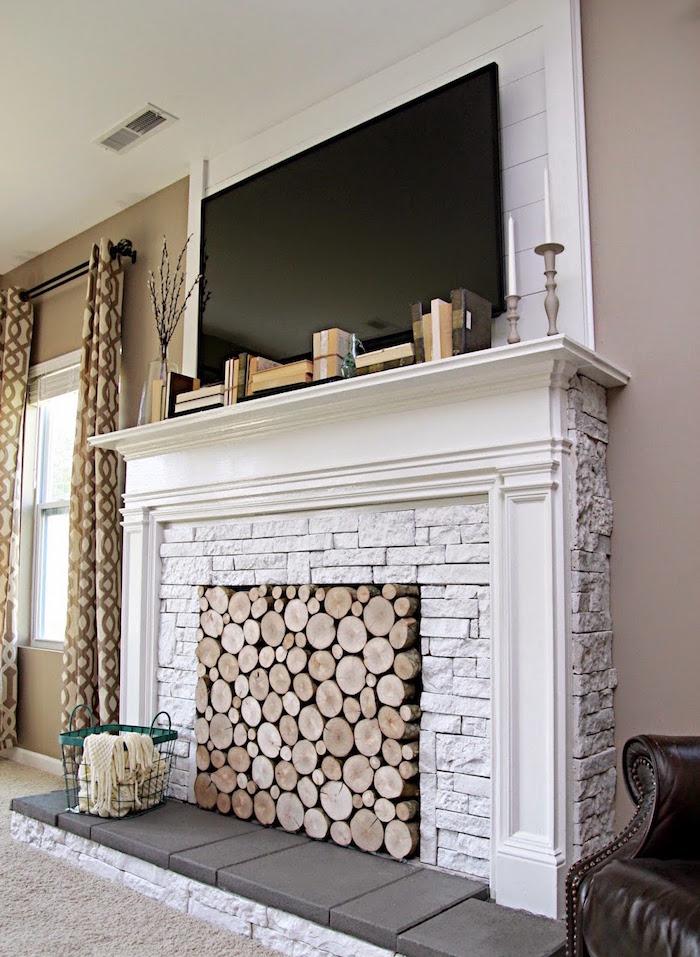 cheminée décorative fausse en pierres blanches comme support tv et foyer rempli de buches en bois