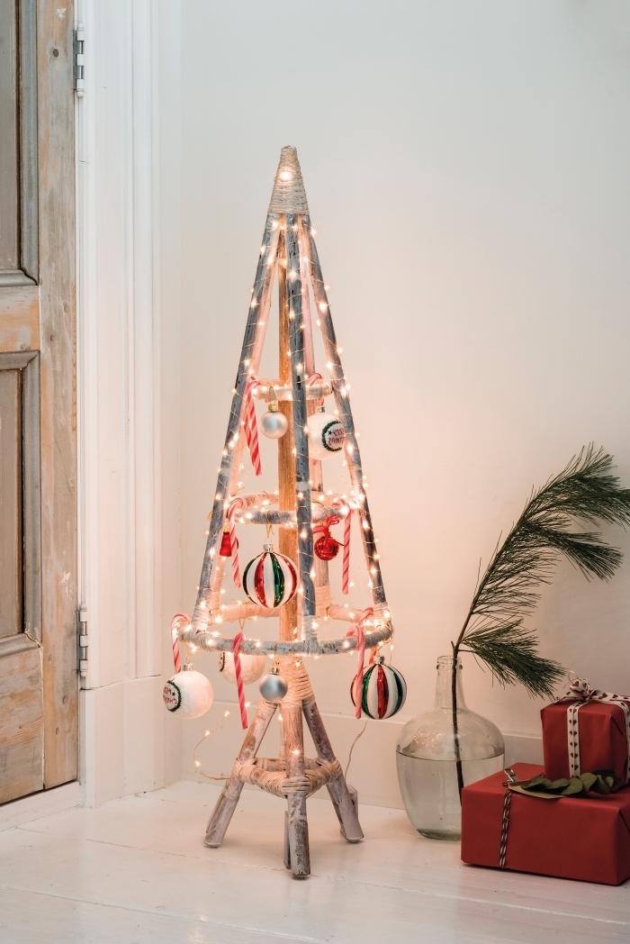 une alternative originale à l'arbre de noël classique, un sapin de noel en bois rustique et vintage à piétement trépied, orné de suspensions de noel traditionnelles en blanc, rouge et vert et d'un' guirlande lumineuse led
