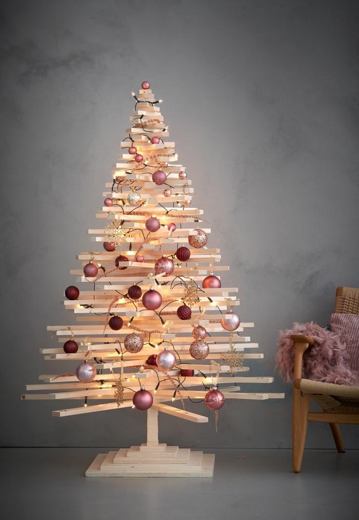 un sapin de noel en bois réalisé à partir d'une multitude de tasseaux croisés avec un pied en bois, décoré avec des boules de noel en tons cuivrés