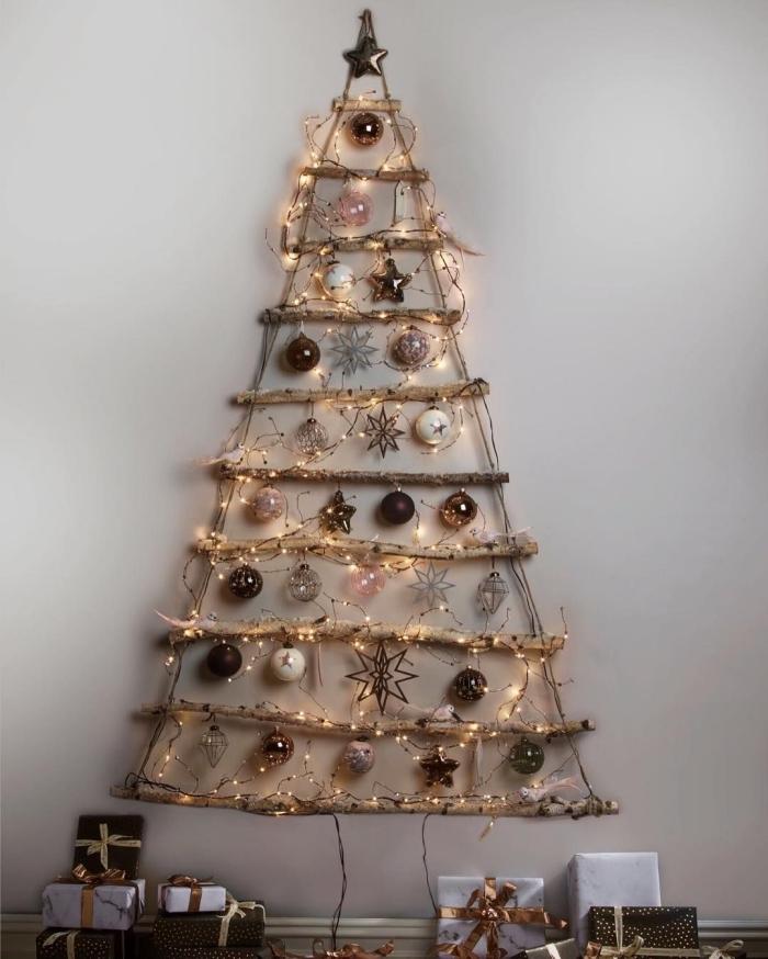 modèle de sapin de noel en bois réalisé avec des branches de bois accrochées au mur et décorées de petits ornements de noël dans les tons de l'or et du cuivre