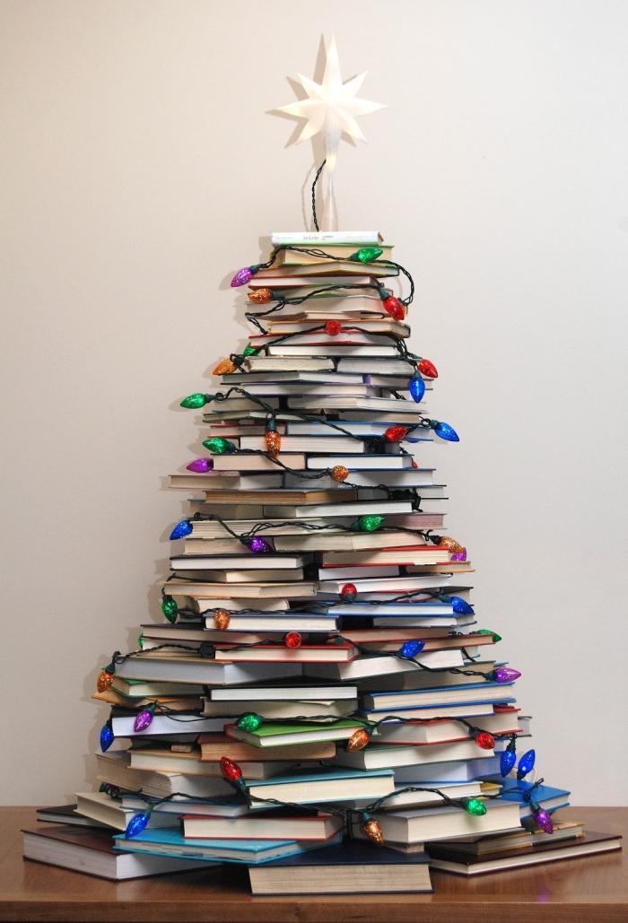 sapin de noël pas comme les autres réalisé avec des livres empilés ornés d'une guirlande lumineuse et d'une jolie étoile blanche