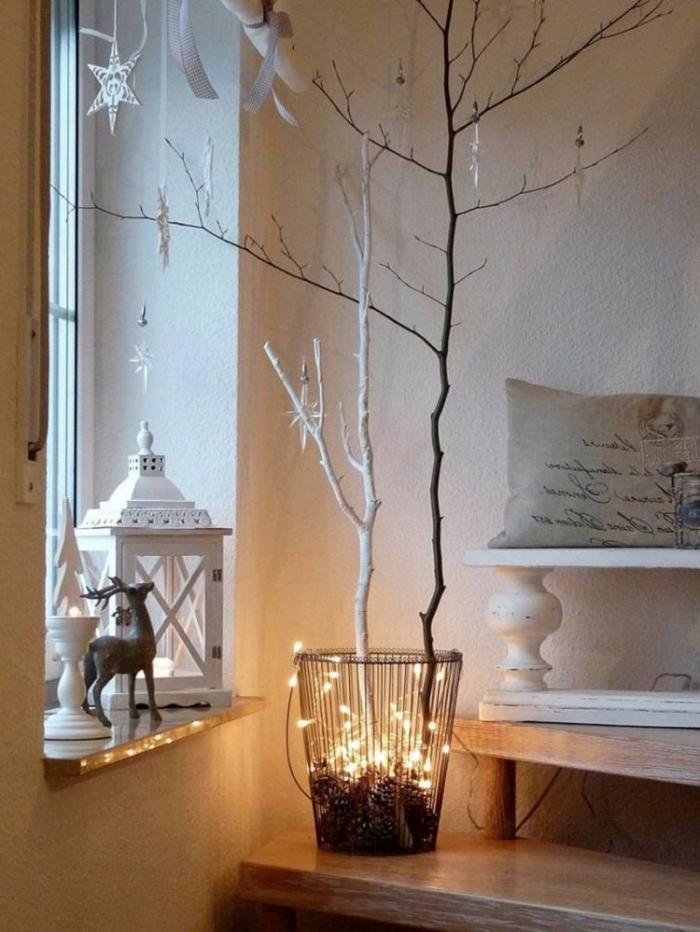 décoration rebord de fenêtre avec une lanterne en métal blanc, un bougeoir et une figurine de cerf, décoration de noel à fabriquer en bois, branches d'arbre en corbeille décorées avec une guirlande lumineuse