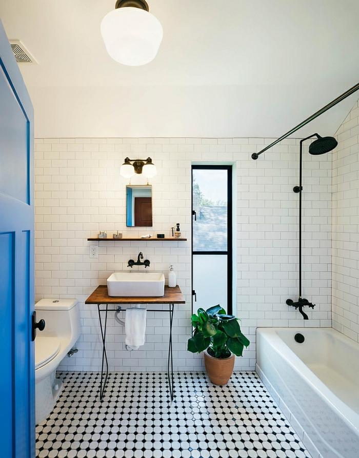 carrelage vintage noir et blanc, pot de fleur, baignoire rectangulaire, carreaux métro, meuble sous vasque recyclé en bois, porte bleue