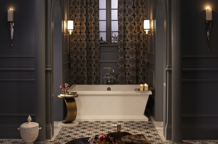 salle de bain gris et blanc, carreaux de ciment, baignoire blanche aux lignes droites, petit tabouret métallique, murs gris, rideaux lourds motifs géométriques