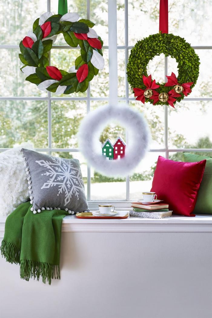 trois couronnes de noël aux couleurs traditionnelles de la fêtes suspendues à la fenêtre avec un rebord décorés avec coussins blanc, rouge, vert et gris transformé en coin lecture cosy