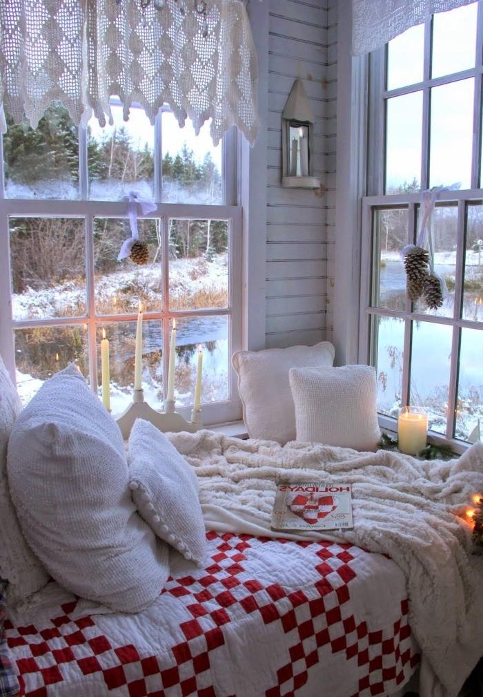 petit coin cocooning aménagé près des fenêtres, aux couleurs traditionnelles pour noël, ornements de noël de pommes de pin attachées aux fenêtres avec un ruban blanc