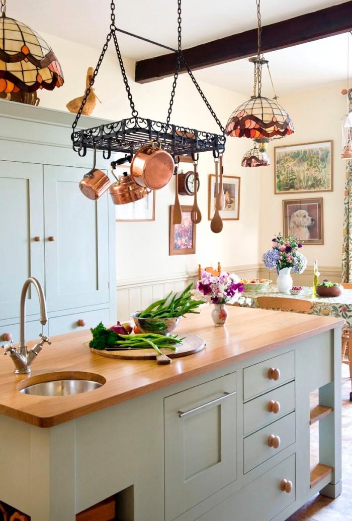 une cuisine de style campagne chic équipée d'un îlot central avec évier et espace de rangement, au-dessus duquel un support à chaudrons a été suspendu, astuces rangement pour mieux organiser sa vaisselle, porte-ustensiles métallique de cuisine à suspendre