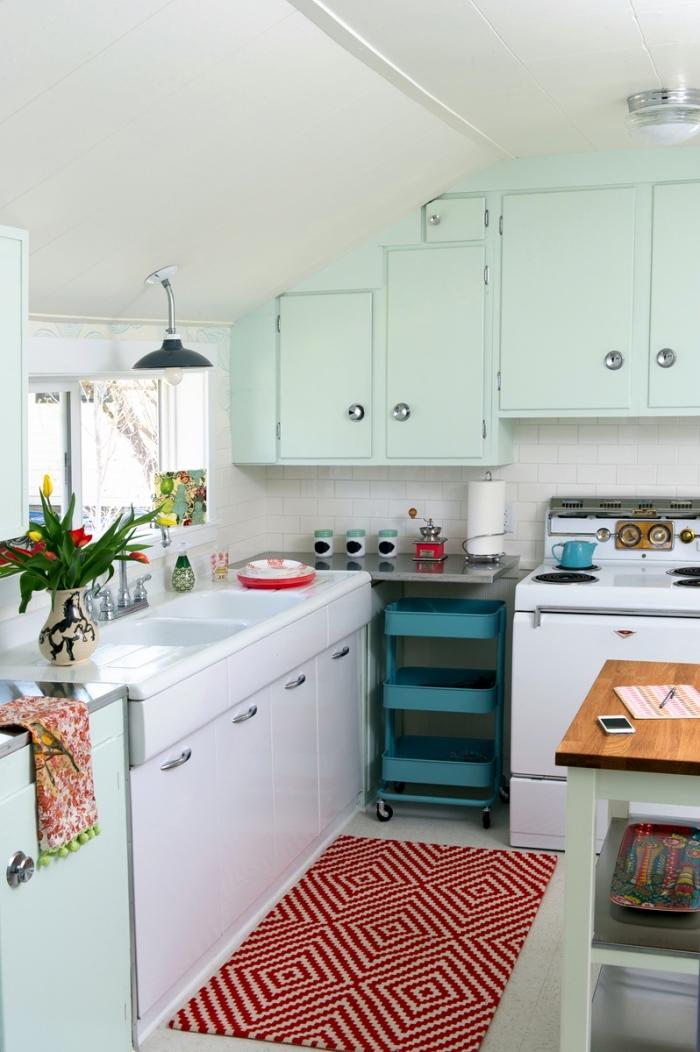 astuces pour aménager une petite cuisine sous pente, des placards de cuisine en blanc et vert menthe à l'eau qui donnent un côté vintage à l'espace, petite cuisine équipée d'un îlot central et d'une desserte d'ikea à roulettes glissée sous le plan de travail