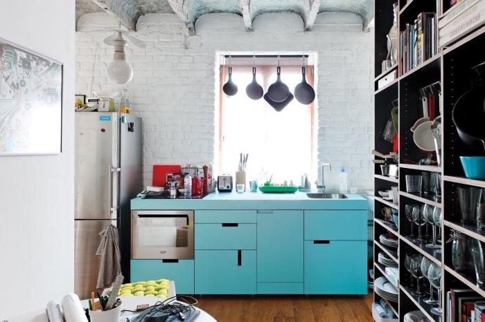 l'amenagement petite cuisine industrielle équipée d'un îlot bleu multi fonctions et d'un meuble de rangement haut à multiples compartiments, aux murs de briques blanches