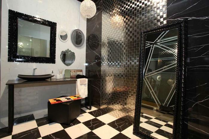 petite sale de bain en noir et blanc, carreaux mosaiques, revêtement mural à finition couleur métallique, miroirs décoratifs, coiffeuse avec tabouret