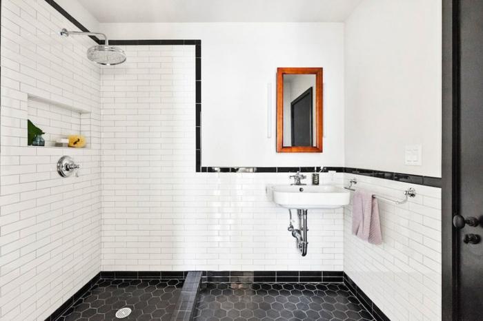 petite salle de bain coquette, sol en carreaux géométriques noirs, lavabo suspendu, tuyauterie apparente, miroir cadre en bois