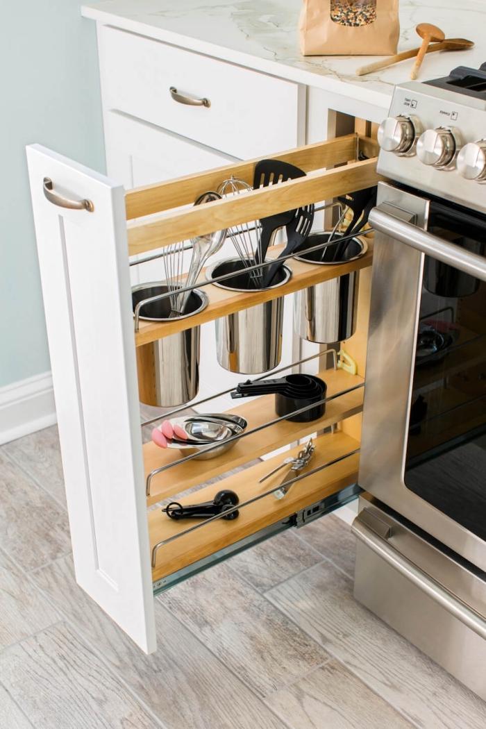 solution ingénieuse pour l'amenagement placard cuisine fonctionnel, un placard étroit bas coulissant avec des porte-ustensiles intégrés et deux tablettes étroites