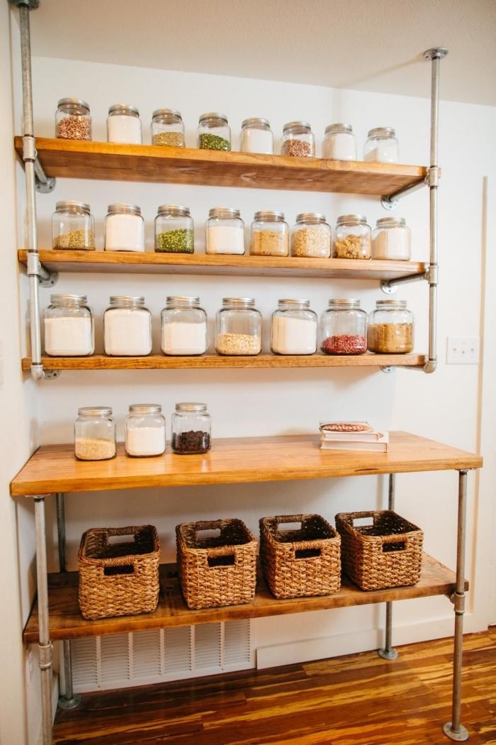 un meuble rangement cuisine en bois et métal de style industriel qui permet d'organiser ses aliments et y accéder facilement, étagère murale en bois et tuyaux récup métalliques installé au-dessus d'une table de service industrielle