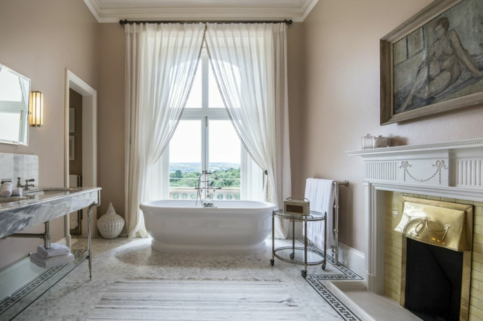 salle de bain spacieuse, tapis rayé couleurs claires, rideau blanc, grand lavabo marbré, cheminée, portrait de femme encadré