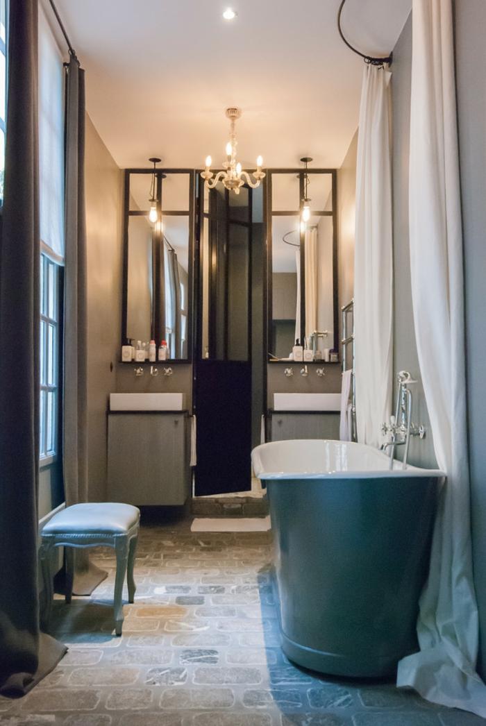 salle de bain en bleu et blanc, tabouret turquoise, miroirs décoratifs, lavabos avec placards compactes, chandelier baroque, grande baignoire turquoise