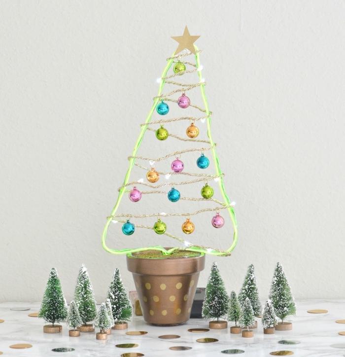 un arbre de noel artificiel en pot sculpté en fil de fer vert fluo et décoré d'une guirlande lumineuse led et de petites boules de noel colorées