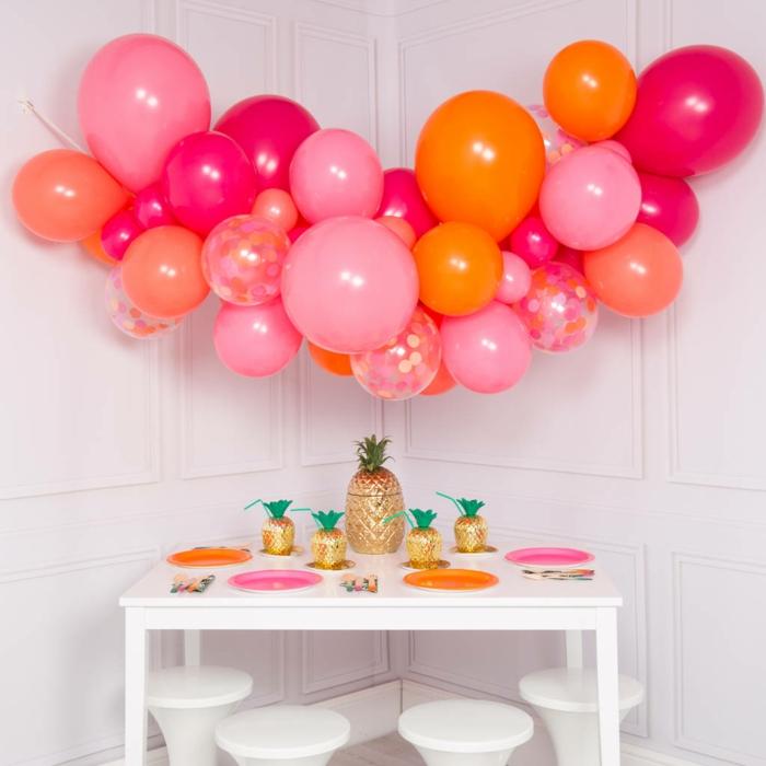 table basse blanche décorée d'assiettes colorées, ballons regroupés ensemble en forme d'arche et suspendus au mur