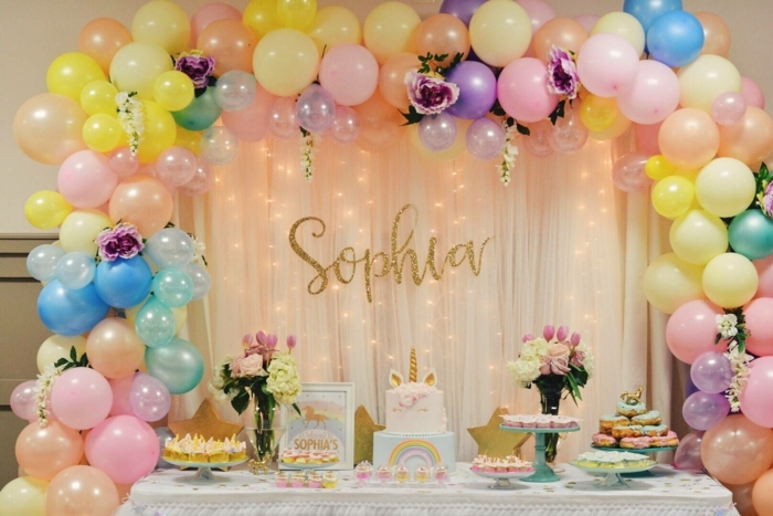 anniversaire de petite fille, ballons attachés ensemble suspendus au-dessus de la table, bouquets de roses, gateau licorne, muffins