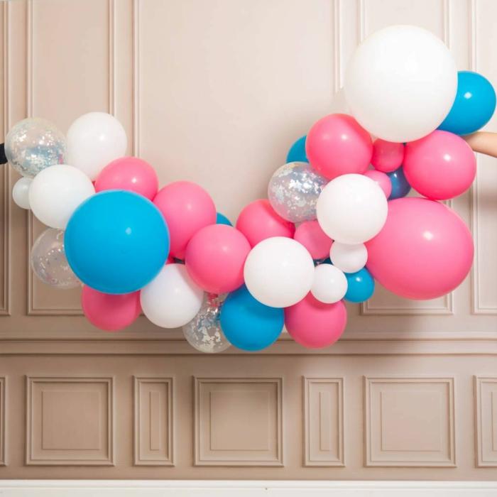arche de ballons en couleurs sucrées, ballons aux paillettes, ballons roses et bleus, mur blanc