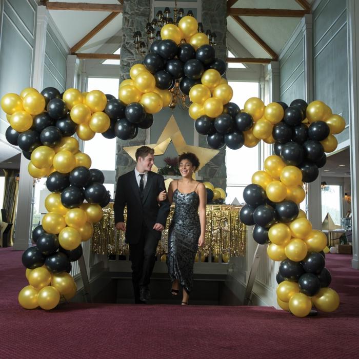 déco de ballons étoile en ballons noirs et jaunes, jeune couple, homme en costume et femme en robe officielle, grand plafonnier