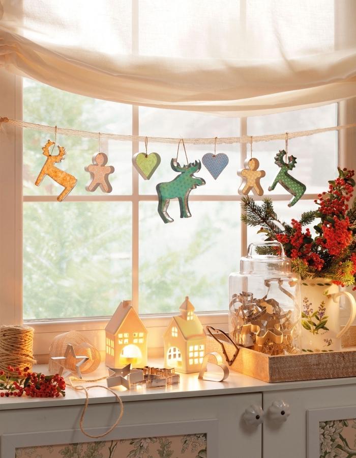 deco noel a fabriquer soi-même, une guirlande de noël réalisée avec des emporte-pièces, suspendue à la fenêtre, déco rebord de fenêtre festive avec des lanternes en papier, une cloche en verre et un vase vintage de branches de sapin