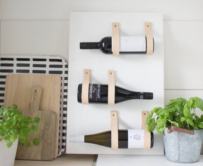 un range-bouteilles réalisé avec une planche en bois et des sangles de cuir, idée pour un rangement à faire soi meme pour exposer ses bouteilles de bin