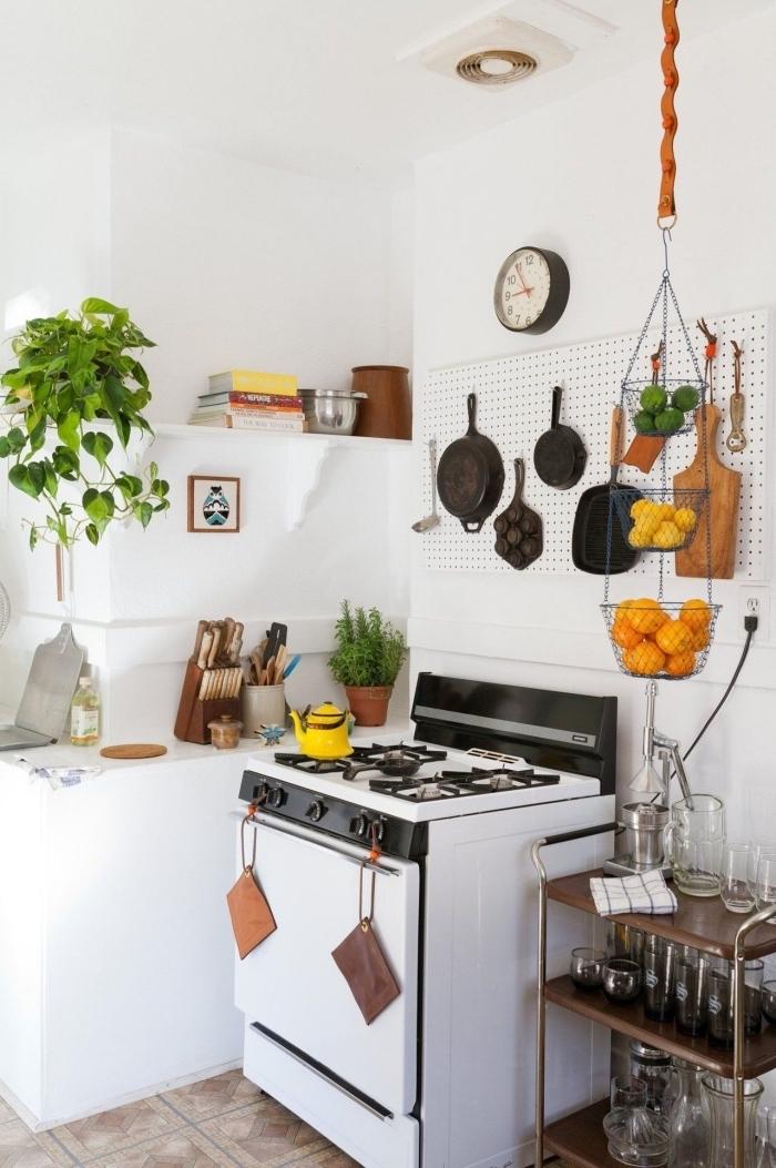 astuces de rangement pour l'amenagement petite cuisine fonctionnelle, un panneau perforé blanc accroché en dessus la cuisinière et transformé en tableau d'accrochage pour les ustensiles de cuisine