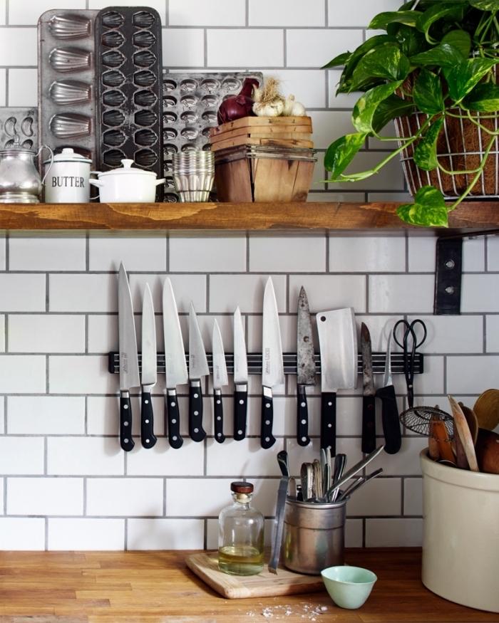 une barre porte-couteaux magnétique fixée au mur en carrelage métro blanc, au-dessous d'une petite étagère en bois portant des moules à biscuits, idée rangement pour gagner de l'espace dans une petite cuisine