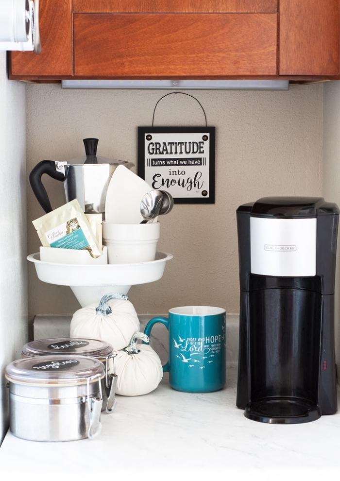 aménager un petit coin café dans la cuisine sur un bout du comptoir avec des boîtes à couvercle métalliques, une machine à café et un plateau sur pied qui accueille tout le nécessaire pour préparer ses boissons chaudes