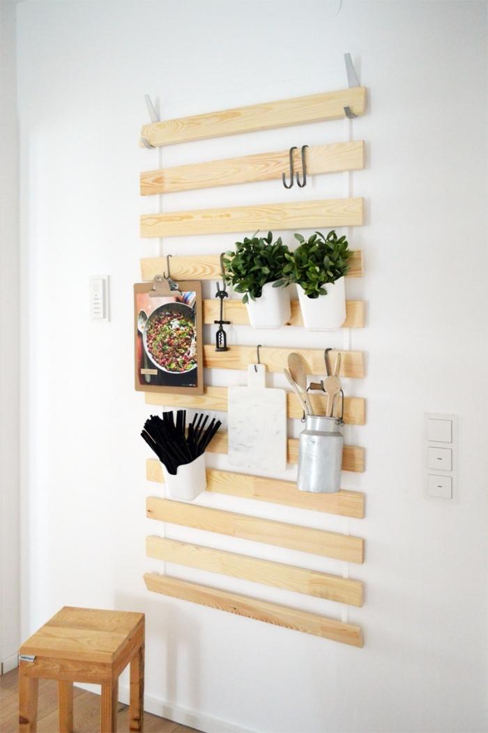 astuce deco ikea pour détourner un sommier de lattes en rangement de cuisine mural sur lequel on suspend des porte-ustensiles, pots d'herbes et des objets déco