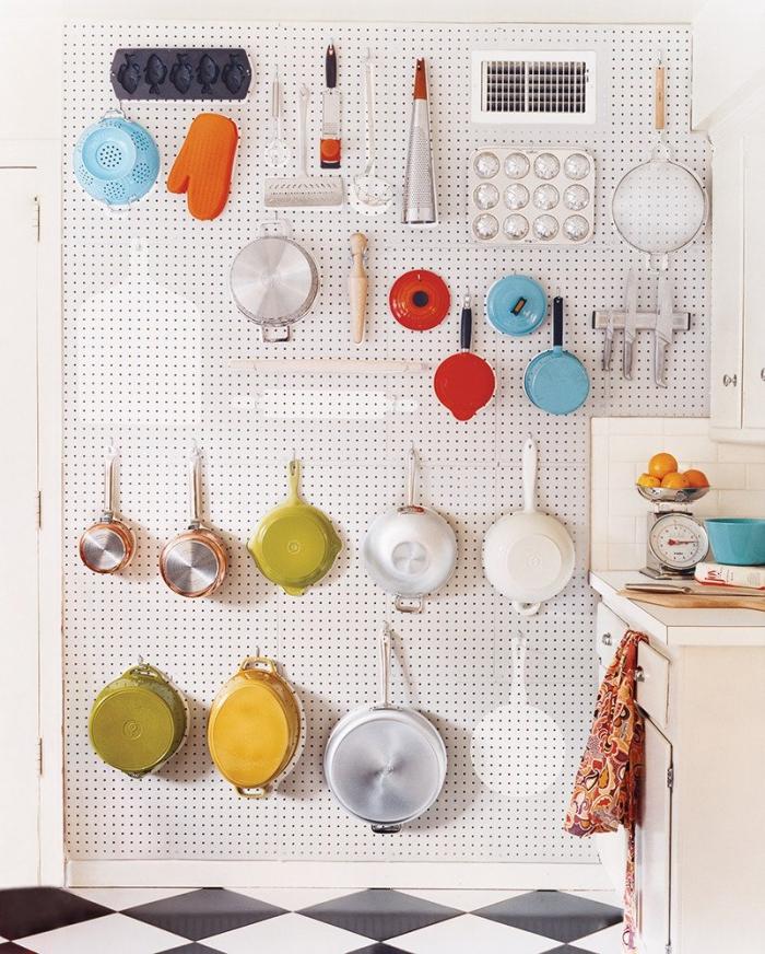 astuce deco pour donner un côté vintage à la cuisine tout en réalisant un rangement mural fonctionnel pour tous les ustensiles de cuisine avec un tableau pegboard perforé installé au mur avec crochets pour y supendre les ustensiles de cuisine, un sol pvc à motif damier noir et blanc
