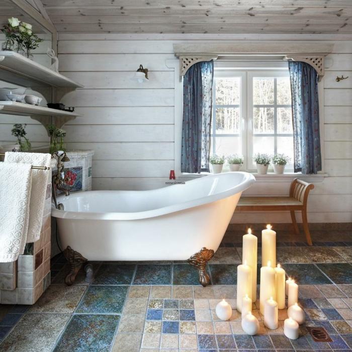 salle de bain en bleu et blanc, bougies allumées, sol mosaique rideaux bleus, étagères blanches, baignoire sabot blanche, murs en lambris blanc