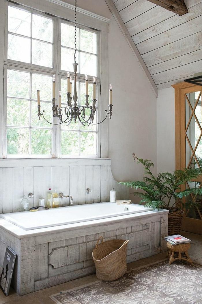 baignoire blanche rectangulaire, grand chandelier vintage, plafond de salle de bain sous pente, plante verte