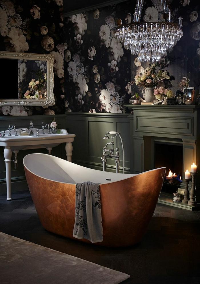 grande baignoire cuivrée au centre de la salle d'eau rétro, grand plafonnier cristal, lavabo remarquable, papier peint noir aux fleurs roses, bougies allumées