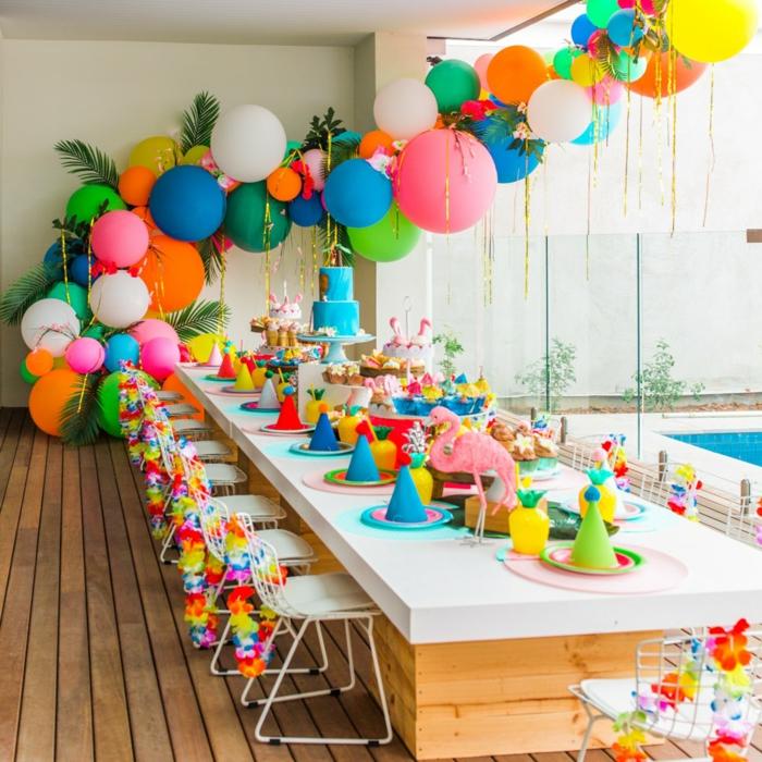 longue table de fête arrangée pour un party coloré, table bois et blanc, grande guirlande de ballons et guirlandes en papier aux chaises