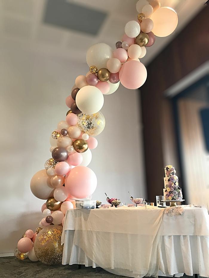 jolie arche mariage en ballons roses et mini ballons aux couleurs métalliques, grands ballons aux confettis, table arrangée