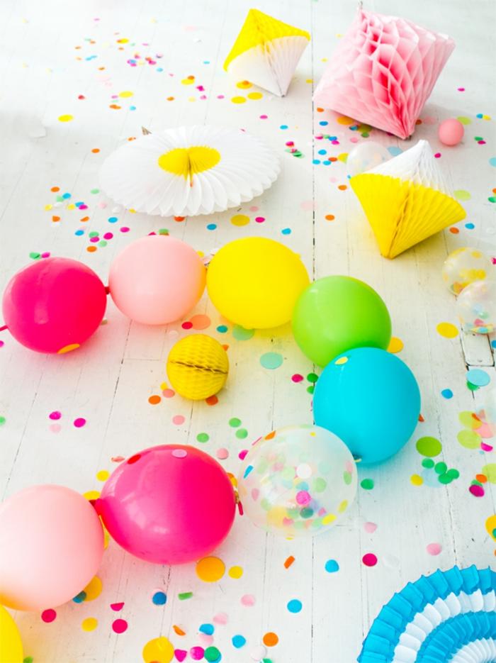 chaîne de ballons en couleurs vives, pinatas de papier décoratif, confettis sur un plancher en planches blanches