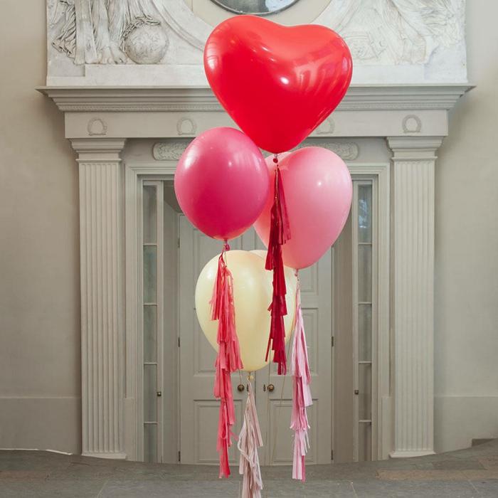 ballons en forme de coeurs liés qui flottent en l'air près d'une grande porte blanche, franges décoratives