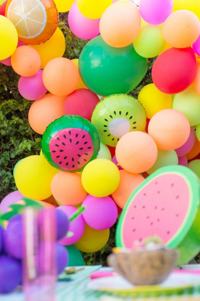 guirlande de ballons fruits tropicaux, ballons pour un party assemblés dans le jardin, ballon kiwi et ballon pastèque