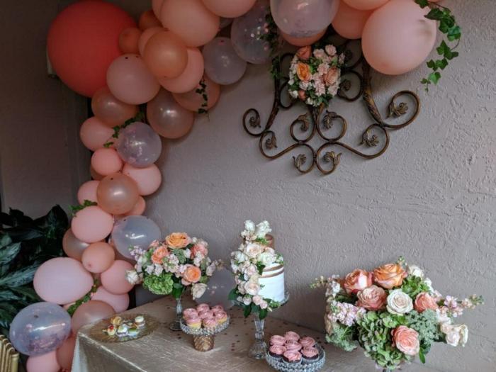 ballons roses oranges et gris groupés en jolie arche attachée au mur gris, bouquet de fleurs, cupcakes roses, plante verte