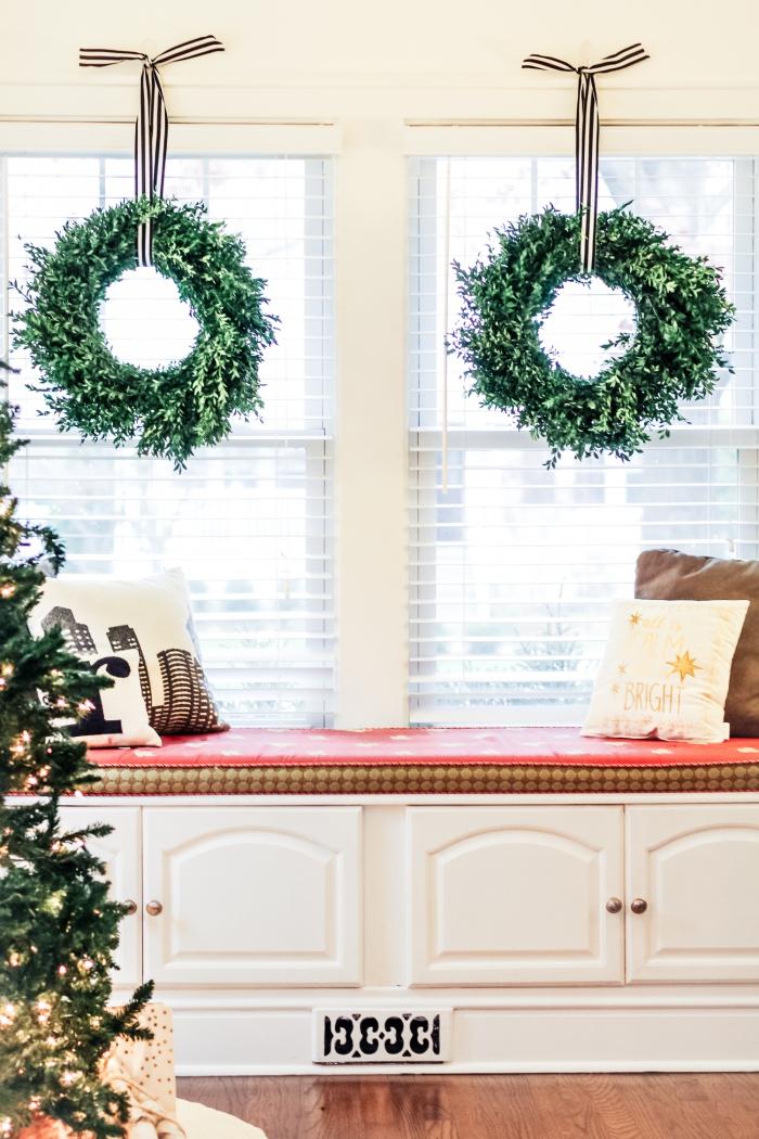 couronnes de noël végétales symétriques accrochées en dessus de la fenêtre, une banquette cosy aménagée près de la fenêtre