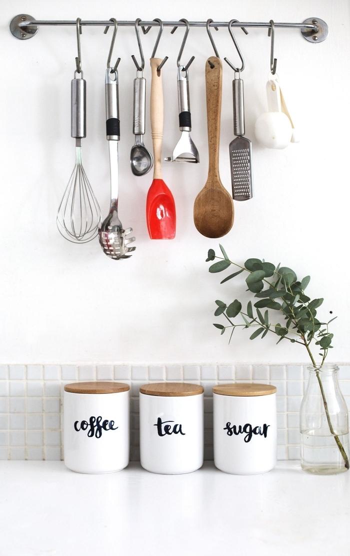 une barre métallique murale avec crochets pour suspendre ses ustensiles de cuisine, trois pots blancs avec couvercles en liège pour le café, le thé et le sucre