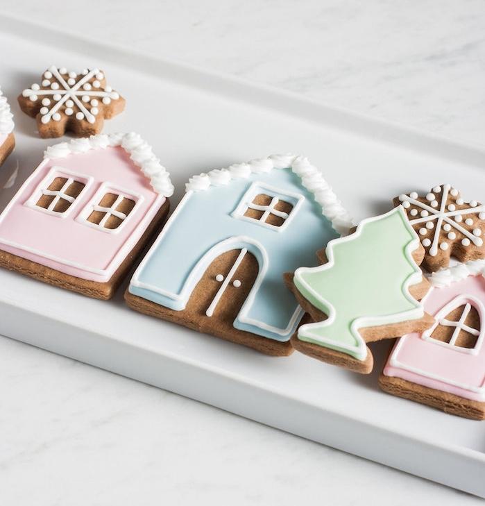 biscuit de noel en pâte pain épice en forme de maisonnette, sapin de noel et flacon de neige avec glaçage coloré tons pastel