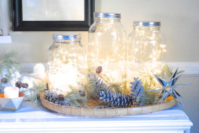 exemple de décoration de noel à fabriquer pour adultes, bocal en verre avec guirlande lumineuse, composition décorative en branches et pommes de pin