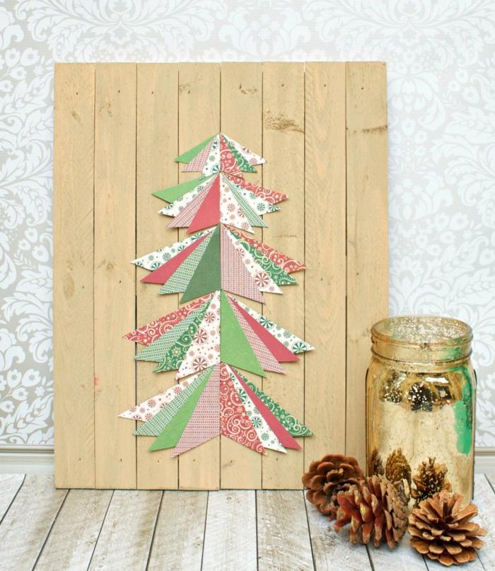 pot de verre, pommes de pin, panneau de palette avec morceaux de papier décoratif collés en forme de sapin