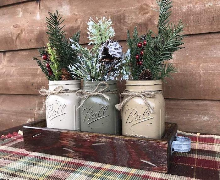 recyclage bocaux en verre avec des branches de pin, houx et pommes de pin dans un plateau rustique de bois brut